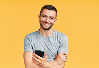 Handsome smiling man holding mobile phone and looking to camera in yellow studio background