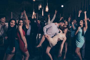 Nice-looking attractive glamorous cheerful cheery positive elegant stylish ladies and gentlemen having fun weekend tango in modern fashionable luxurious nightclub indoors