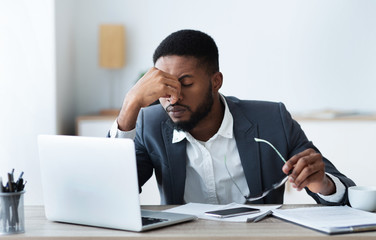 African american businessman tired of long time work on laptop