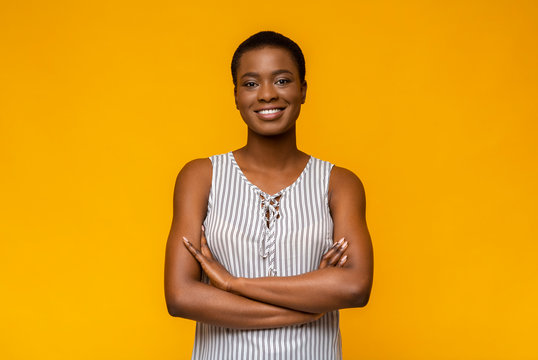 Confident african american woman posing on yellow studio background