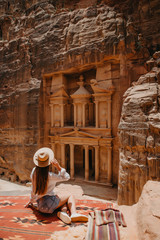 Young woman tourist sitting on a cliff after reaching the top, Al Khazneh in the ancient city of Petra, Jordan, UNESCO World Heritage Site