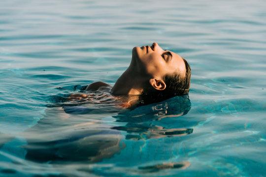 Young woman swim in the swimming pool