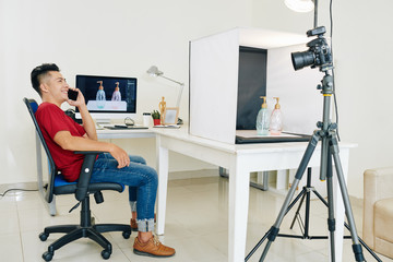 Happy stock photographer sitting in chair and talking on phone after retouching photos of dispensers he made in his studio