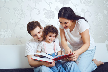 Mother and father with children read a book while sitting on a sofa