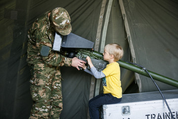 Soldier introducing anti-aircraft air defence simulator to a boy child.