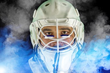 Detail of a male face in a white goalie hockey mask and  blue and white smoke.This is a detail hockey goalie. He is concentrated on game. He has blue and white color under his eyes.