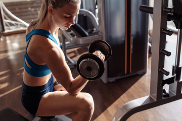 Top view of a concentrated strong young beautiful woman working out with dumbbells in the gym. The concept of sports loads for body beauty and body care