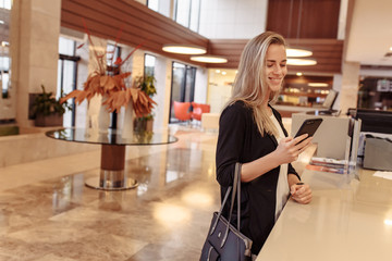 Positive smiling young woman, a blonde millennial, looks at mail in social networks and joyfully answers messages while checking into her hotel room. Travel and gadget concept