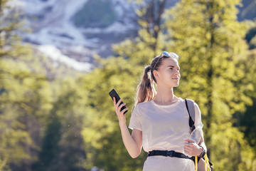 Portrait of a beautiful young female traveler with a smartphone in her hands traveling through the mountains. Concept of navigators and applications for travelers