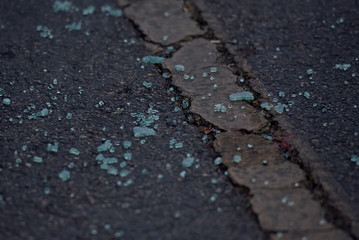 Shattered glass is seen on the pavement next to a car with a broken window at a grocery store parking lot following Saturday's shooting in Odessa, Texas