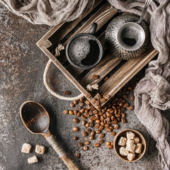 Fototapete - Coffee on wooden tray with coffee beans on dark textured background. Top view with copy space. Background with free text space.