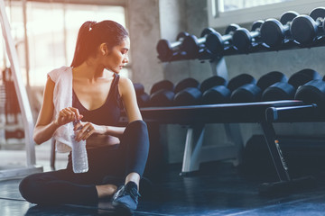 Foto auf AluDibond Fitness Fit young woman sitting and resting after workout or exercise in fitness gym. woman at gym taking a break and relax with water in sportswear. Fitness concept, Healthy, Sport, Lifestyle