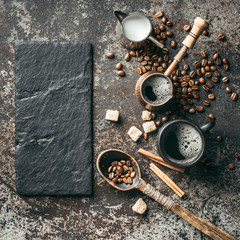 Wall Mural - Coffee cup, sugar, milk and coffee beans on dark background.