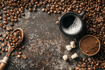 Wall Mural - Coffee cup and coffee beans on dark stone background. Top view with copy space. Background with free text space.