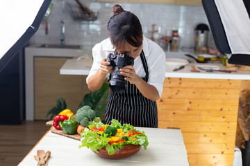 photographer food , asian women is taking pictures of food her food in studio.