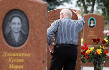 A man mourns at the cemetery, where victims of the 2004 school siege are buried, in Beslan