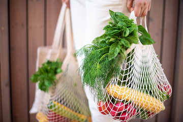 Zero waste concept with copy space. Woman holding cotton shopper and reusable mesh shopping bags with vegetables, products. Eco friendly mesh shopper. Zero waste, plastic free concept. Wall mural