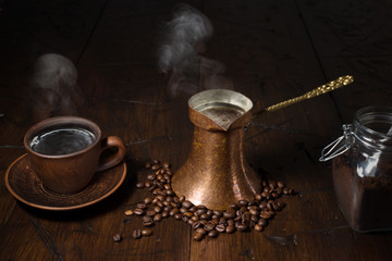Cup of coffee, cezve and a jar of ground coffee on a wooden table.