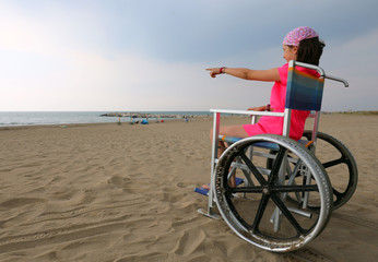 young girl on the wheelchair with pink bandana in summer