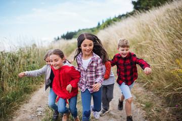 Group of school children running on field trip in nature.