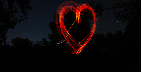 Heart drawn by fire on a dark background. Red heart on a black night background. Love, romantic and festival concept