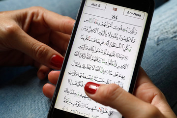 Young Muslim woman reading a digital Quran on a smartphone, Vietnam