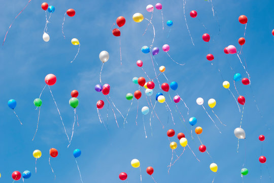 Multi-colored helium balloons fly in the sky