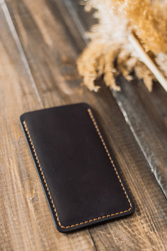 Expensive, beautiful cover of eco-leather on a background of wood and wheat. Beautiful nature care concept. Handmade phone case in black color