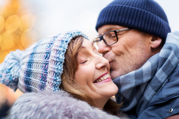 love, christmas and people concept - close up of happy senior couple kissing outdoors in winter