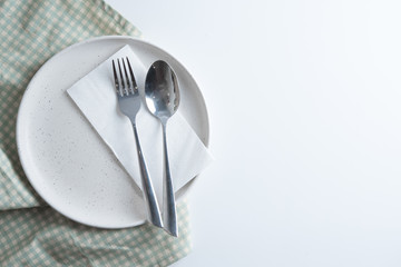 Empty plate with spoon and fork at napkin