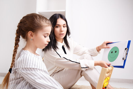 Therapist showing to the little patient smiling face on the paper. Psychologist consept