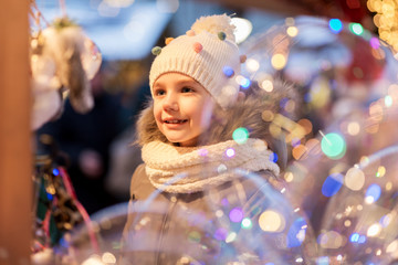 holidays, childhood and people concept - happy little girl at christmas market in winter evening
