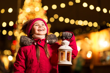 holidays, childhood and people concept - happy little girl with lantern at christmas market in winter evening Fotomurales