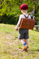 Rural Way to School / Cute little elementary schoolboy seen from back walk outdoor way to school in nostalgic clothes and satchel (copy space)