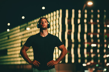 Young sports man taking a break during a night jogging