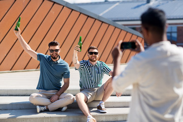 leisure, male friendship and people concept - man with smartphone photographing his friends toasting beer on street in summer