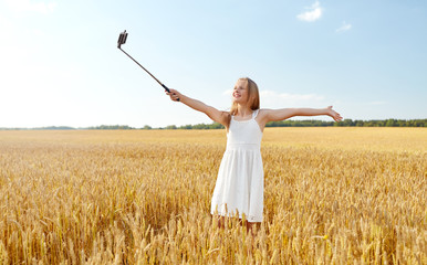 technology, summer and people concept - happy young girl in white dress taking picture by smartphone on selfie stick on cereal field