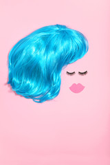 Blue wig with eyelashes and paper lips on pink background. Minimalism concept