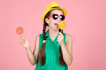 Beautiful young girl with sweet lollipops on pink background Fototapete