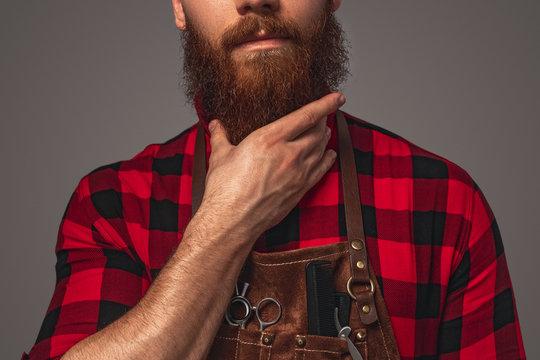 Crop stylish hairdresser stroking beard
