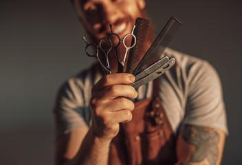 Crop man showing barber tools