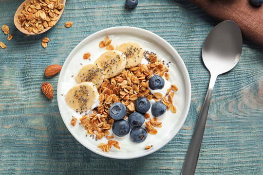 Bowl of yogurt with blueberries, banana and oatmeal on color wooden table, flat lay
