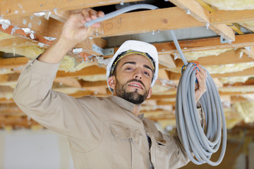 worker in the attic connects air ducts