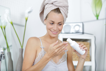 woman in towel on head putting cream on