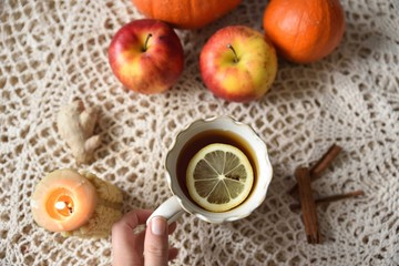 Hand taking cup of warm tea with lemon with pumpkins, apples, candle and spices, fall scene