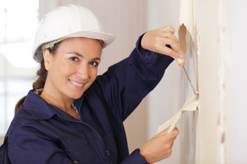 woman plasterer mixing the filler