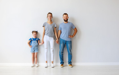 happy family mother father and child  near an empty wall