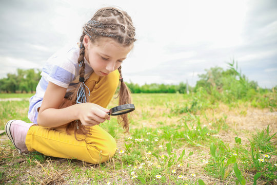 Little girl with magnifying glass studying nature outdoors