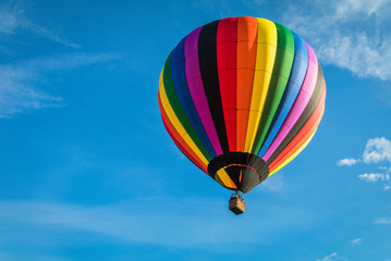 Poster Balloon Rainbow colorful hot-air balloon floats on a summer morning with bright blue sky