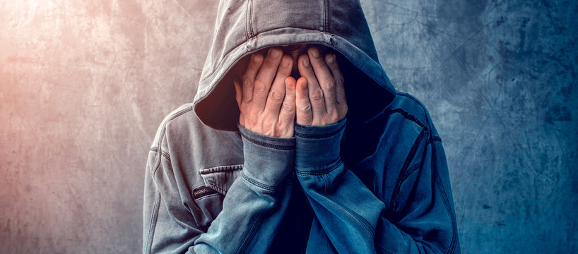 Desperate man in hooded jacket is crying